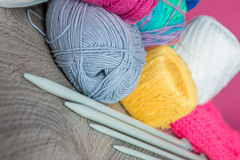 Knitting. Group of yarn and needles on grey wooden table  pink background. Handmade. Close up. Royalty Free Stock Image