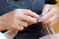 Knitting. Hands of an elderly woman with knitting needles Stock Images