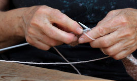 Knitting. Hands of an elderly woman with knitting needles Royalty Free Stock Photo