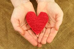 Knitting heart in the hands Stock Image