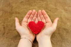 Knitting heart in the hands Royalty Free Stock Photos