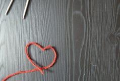 knitting Hilo rojo en fondo de madera Agujas que hacen punto fotos de archivo