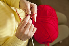 Knitting horizontal. A horizontal format top view of an elderly womans hands as she knits a red sweater royalty free stock images