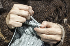 Knitting hour. Two hands doing a knitting stitch Stock Image