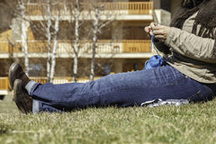 Knitting. Inferior part of young woman body sitting on the grass knitting a scarf Stock Photo