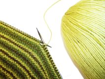 Knitting. Knitted fabric, knitting needles and a skein of yarn. Work process. Hobbies crafts.  stock images