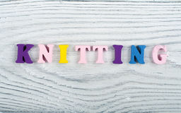 Knitting. Knitted Fabric Texture. Word composed from ABC alphabet letters on wooden background. Royalty Free Stock Photo