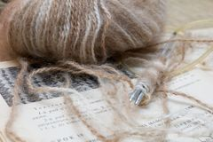 Knitting lesson. Wool ball and knitting accessories on a textbook Royalty Free Stock Images