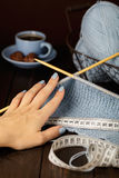 Knitting from light blue yarn. Female hand and centimeter. Stock Image