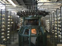 Knitting Machine & Creels in a Factory. Manufacturing of knitted cotton fabric in its raw state prior to dyeing Royalty Free Stock Photography
