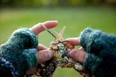 Knitting Man. Man (with hand warmers) knitting new garment Royalty Free Stock Photography