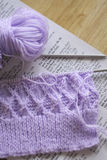Knitting on needles. Lilac knitting wool on needles and the pattern beneath Royalty Free Stock Images