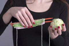 Knitting needles and ball of wool in a woman`s hands Royalty Free Stock Image