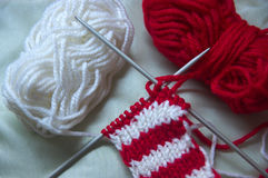Knitting needles crossed with red and white balls on neutral background Royalty Free Stock Photos