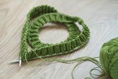 Knitting needles, and green wool yarn Stock Photography