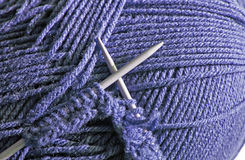 Knitting needles with knitted stitches using blue wool Stock Images