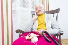 Knitting old lady. Elderly lady knitting for her family from white yarn Stock Image