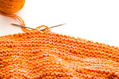 Knitting, orange wool on white Stock Images