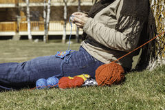 Knitting outdoor. A relaxed woman knitting outdoor Royalty Free Stock Image