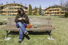Knitting outdoor. A young woman knitting in a park Stock Photography