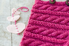 Knitting pattern and felt hearts on a  background Royalty Free Stock Image