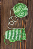 Knitting pattern of green yarn on a wooden background Royalty Free Stock Photo