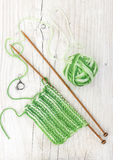 Knitting pattern of green yarn on wooden needles Stock Image