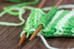Knitting pattern of green yarn on wooden needles Royalty Free Stock Photography