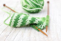 Knitting pattern of green yarn on wooden needles and skein Royalty Free Stock Photos