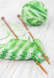 Knitting pattern of green yarn on wooden needles on a wooden bac Royalty Free Stock Photo