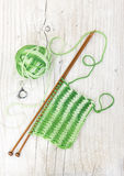 Knitting pattern of green yarn on wooden needles on a wooden bac Stock Images