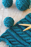Knitting pattern and needles on a wooden background Royalty Free Stock Photos