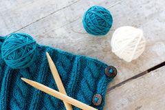 Knitting pattern and needles on a wooden background Royalty Free Stock Photography