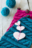 Knitting pattern on a wooden background and heart felt Stock Image