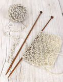 Knitting pattern of yarn on wooden needles Stock Photo