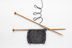 Knitting. Piece of grey knitting on knitting needles Stock Images