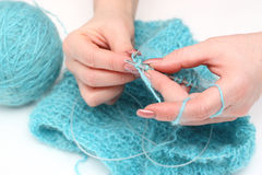 Knitting a pullover. Woman hands knitting a turquoise pullover Royalty Free Stock Images