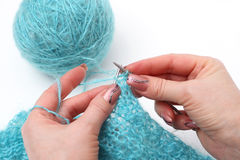 Knitting a pullover. Woman hands knitting a turquoise pullover Royalty Free Stock Photography
