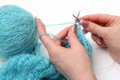 Knitting a pullover. Woman hands knitting a turquoise pullover Stock Photos