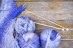 Knitting purple yarn on wooden background/natural wool knitting Royalty Free Stock Photo