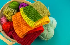 Knitting a rainbow scarf and hat Blue background royalty free stock image