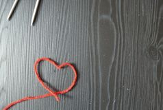 Knitting. Red thread on wooden background. Knitting needles stock photos