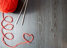 knitting Rode draad op houten achtergrond Breinaalden stock fotografie