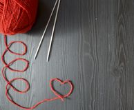 knitting Rode draad op houten achtergrond Breinaalden royalty-vrije stock afbeelding