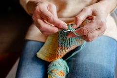 Knitting a scarf with colorful melange threads. Woman Knitting a scarf. Hands holding threads. Colorfull Knitting with colorful melange threads stock image