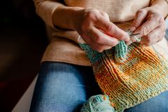Knitting a scarf with colorful melange threads. Woman Knitting a scarf. Hands holding threads. Colorfull Knitting with colorful melange threads stock images