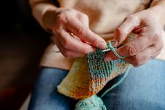 Knitting a scarf with colorful melange threads. Woman Knitting a scarf. Hands holding threads. Colorfull Knitting with colorful melange threads stock photos