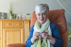 Knitting Senior. One Senior Woman sitting with knitting in her chair in the living room Stock Photo