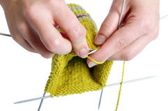 Knitting a sock. A half way knitted yellow wool sock on white background Royalty Free Stock Photo