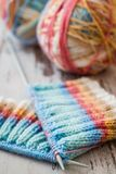 Knitting with Spokes. Colorful knitting with spokes and ball of yarn on white wooden table royalty free stock photography